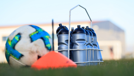 Foto de Ecological sport bottles of fresh water, beverage on soccer field grass. Blurred soccer ball, cone. - Imagen libre de derechos