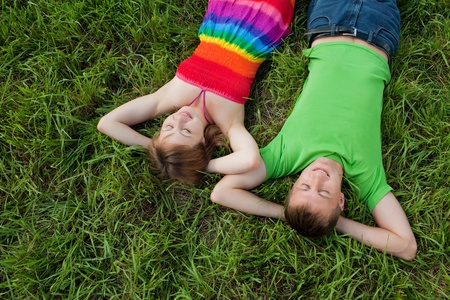 Couple lying on grass and enjoys