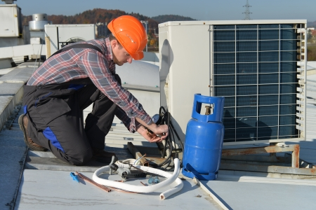Air Conditioning RepairYoung repairman on the roof fixing air conditioning systemModel is actual electrician