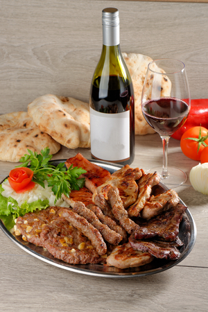 Mixed grill on a plate with excellent wine
