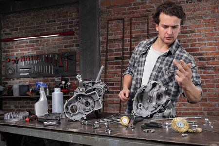 man work choose wrench for repair and cleaning engine parts