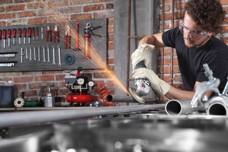 man work in home workshop garage with angle grinder, goggles and construction gloves, metal grinder makes sparks, diy and craft concept.