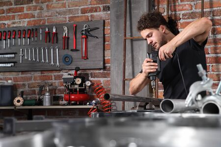 man in home workshop garage work drilling metal with drill, repair iron pipe on the workbench full of wrenches, diy and craft concept.