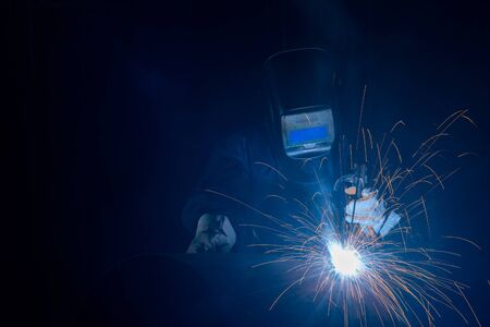 Foto de Professional welder and mask welding metal pipe on the industrial table.A welder is a tradesperson who specializes in fusing materials together. - Imagen libre de derechos
