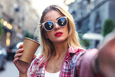 Photo pour Portrait of woman in sunglasses taking photo on the smartphone. - image libre de droit