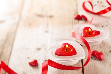 Photo pour Candles, hearts and ribbon on wooden table. - image libre de droit
