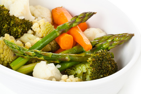 Closeup shot of steamed vegetables on white plate.