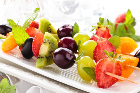 Photo pour Fresh summer fruits on sticks. With mint leaves. - image libre de droit