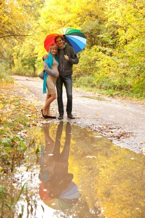Happy pregnant woman and a man walking in the autumn forest under a rainbow colorful umbrella and reflected in a puddle