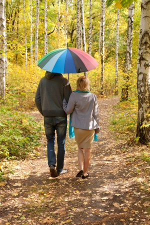 Happy pregnant woman and a man walking in the autumn forest under a rainbow colorful umbrella, rear view