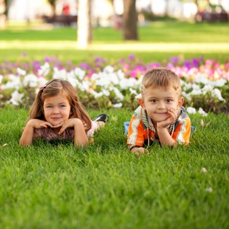 Foto de Little boy and girl relaxing on the grass among flowers. - Imagen libre de derechos