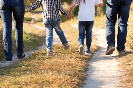 Photo pour Family feet and legs in jeans. Father, mother, son and daughter walking on the road. Rear view. - image libre de droit