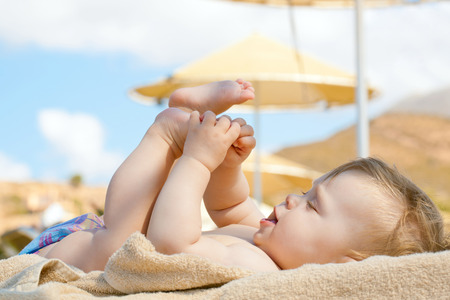 Foto de Happy baby resting on the beach sunbed. 8 month old kid lying on sun lounger and playing with her feet. Summer holidays concept. - Imagen libre de derechos