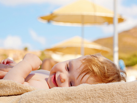 Happy baby sunbathing on the beach sunbed. Summer holidays concept.