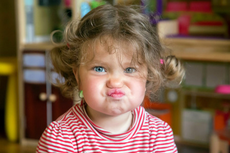 Photo for Funny portrait of adorable baby girl. Child makes grimaces face - Royalty Free Image
