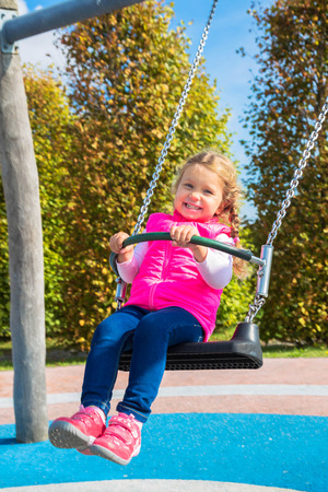 Photo for Little cheerful girl swinging on a swing. Sunny weekend. Baby happiness. - Royalty Free Image