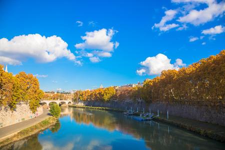 Foto de Autumn city landscape. Trees with yellow leaves, river, blue sky with clouds. Sunny autumn day. - Imagen libre de derechos