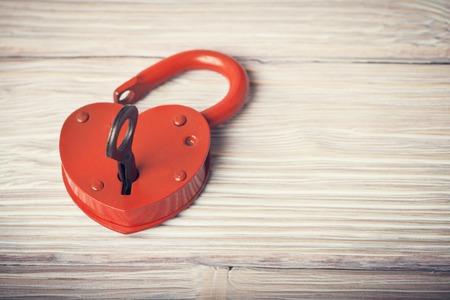 Foto de Open heart shaped lock and key over light vintage wooden background - Imagen libre de derechos
