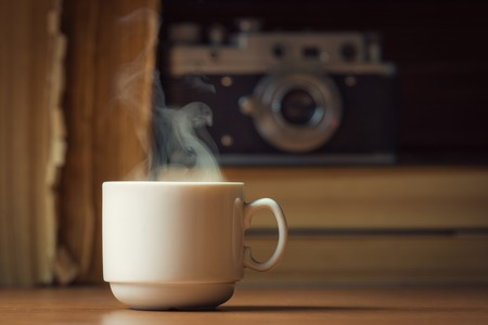 Cup of hot coffee with steam over defocused books and vintage camera