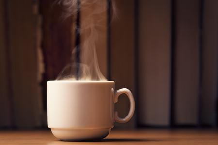 Cup of hot coffee with steam over defocused books background