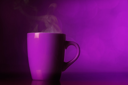 Cup with steam over purple  background