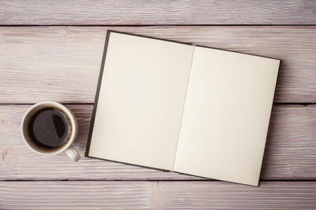 Photo pour Open notebook with cup of coffee on wooden desk - image libre de droit