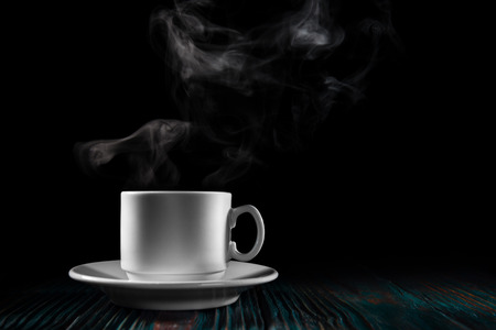 Cup of freshly brewed coffee over  black background