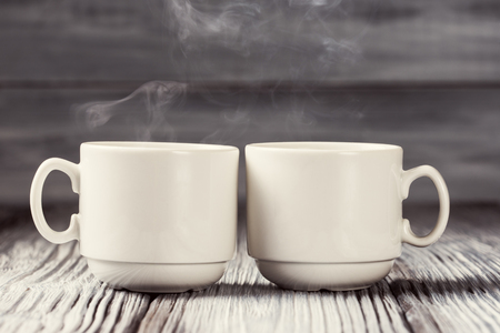Two cups of hot coffee over wooden background