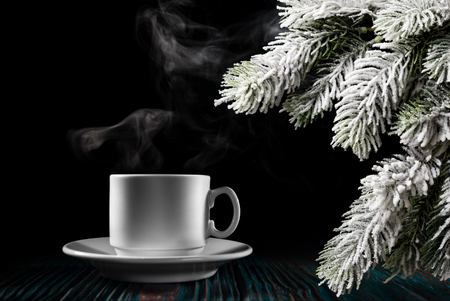 Steaming coffee and Christmas tree branch over black background