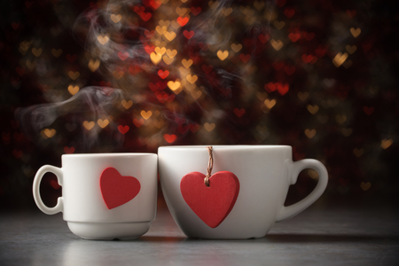 Two steaming cups of coffee over defocused lights on Valentines day