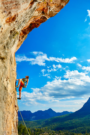Foto de female rock climber climbs on a rocky wall - Imagen libre de derechos