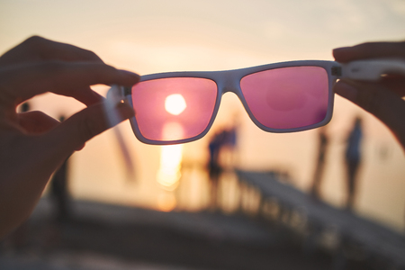 Foto de view of the sun, sea and sky through pink sunglasses at sunset. a look at the world through rose-colored glasses, the idea of illusory and naivety - Imagen libre de derechos