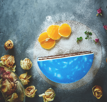 Photo for top view of composition of half of cutted mousse cake with blue glaze, sliced oranges, sugar powder and dried roses on a dark gray concrete background - Royalty Free Image