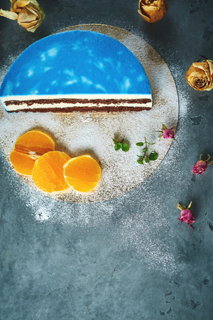 Photo for composition of half of cutted mousse cake with blue glaze, sliced oranges, sugar powder and dried roses on a dark gray concrete background. Top view with copyspace - Royalty Free Image