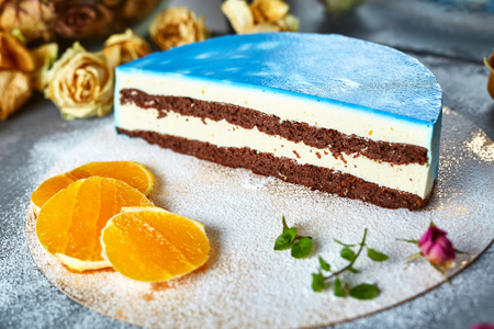 Photo for composition of half of cutted mousse cake with blue glaze, sliced oranges, sugar powder and dried roses on a dark gray concrete background - Royalty Free Image