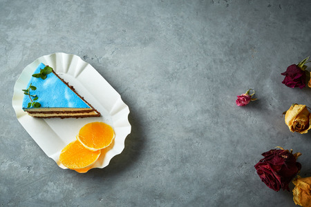 Photo for composition of piece of cutted mousse cake with blue glaze on a white paper dish, sliced oranges and dried roses on a dark gray concrete background. Top view with copyspace - Royalty Free Image