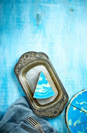 Photo for sliced cake and piece of mousse cake with blue glaze on a looking like silver, vintage metal dish on the white-blue wooden background. fork, knife and blue cloth napkin on the table. Horizontal Top view with copyspace - Royalty Free Image