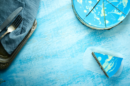 Photo for sliced cake and piece of mousse cake with blue glaze on the white-blue wooden background. Looking like silver, vintage metal dish, fork, knife and blue cloth napkin on the table. Horizontal Top view with copyspace - Royalty Free Image