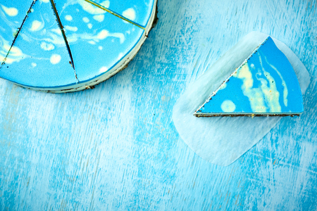 Photo for sliced cake and piece of mousse cake with blue glaze on the white-blue wooden background. Horizontal Top view with copyspace - Royalty Free Image