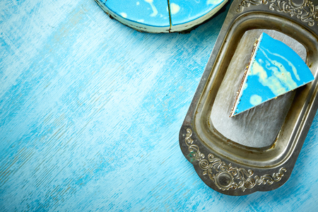 Photo for cutted piece of mousse cake with blue glaze on a looking like silver, vintage metal dish on the white-blue wooden background. Horizontal Top view with copyspace - Royalty Free Image