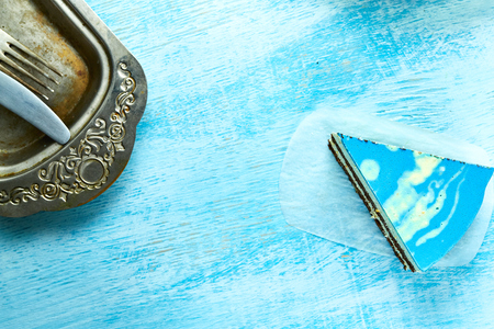 Photo for piece of mousse cake with blue glaze on the white-blue wooden background. Looking like silver, vintage metal dish, fork, knife on the table. Horizontal Top view with copyspace - Royalty Free Image