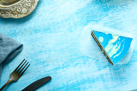 Photo for piece of mousse cake with blue glaze on the white-blue wooden background. Looking like silver, vintage metal dish, fork, knife and blue cloth napkin on the table. Horizontal Top view with copyspace - Royalty Free Image