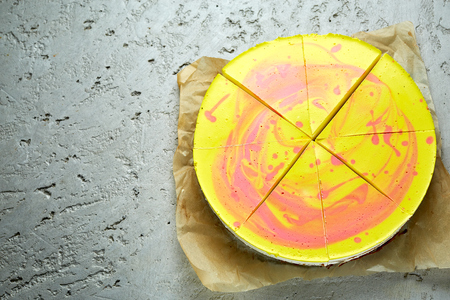 Photo for sliced mousse cake with yellow red glaze on the gray concrete background. Horizontal Top view with copyspace - Royalty Free Image