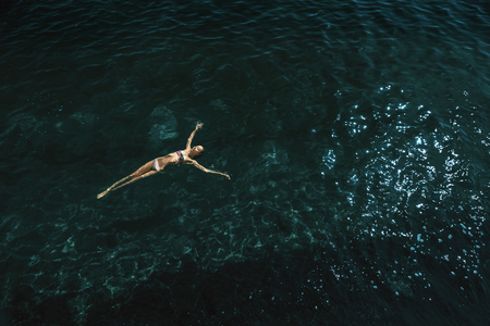 Foto de aerial view of a beautiful sexy slim woman floating and reraxing in the deep blue sea. relaxed woman floating on transparent turquoise sea. Summer seascape with girl and azure water - Imagen libre de derechos