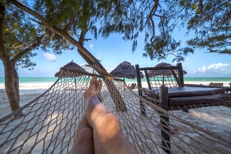 Foto de Mans crossed legs in hammock over tropical lagoon - Imagen libre de derechos
