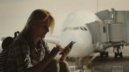 Foto de Woman traveler uses a smartphone in the airport terminal on the background of a large airliner outside the window - Imagen libre de derechos