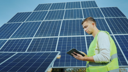 Foto de A worker uses a tablet in a large ground-based solar panel. Alternative energy - Imagen libre de derechos