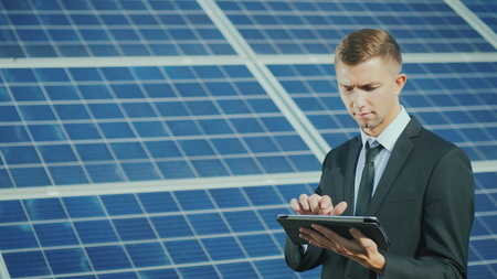 Foto de A young businessman uses a tablet near a solar power station - Imagen libre de derechos