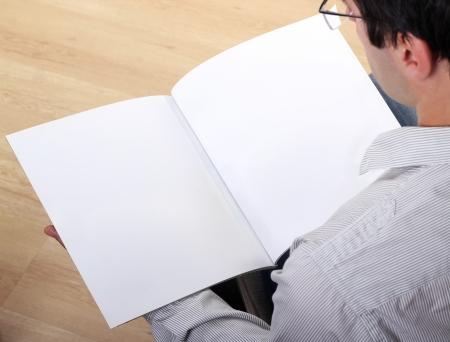 Photo pour Man holds empty brochure  - image libre de droit
