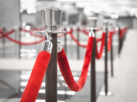 Photo pour Red Carpet fence pole with red ropes Blurred interior background - image libre de droit